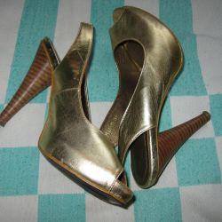 Açık bir burun ile altın ayakkabılar