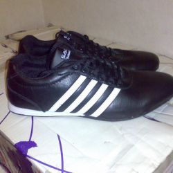 Sneakers are black with a white stripe.