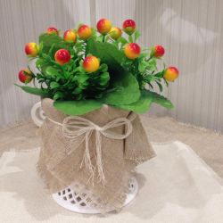 Artificial flowers and berries in a vase for the interior.