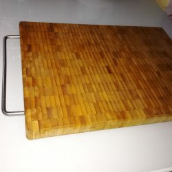 Cutting board made of natural wood with a handle