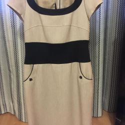 The dress is beige with black accents.