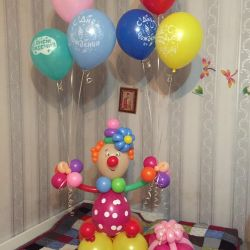 Clown with helium balloons and gift