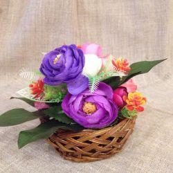 Arrangement of artificial flowers, basket, vase.