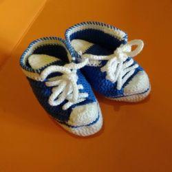 Fotoğraf çekimleri için örme spor ayakkabılar. Bebeğin patik