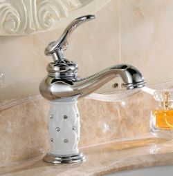 The faucet mixer is chrome with stones in the bath