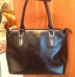 The bag is black. Genuine Leather