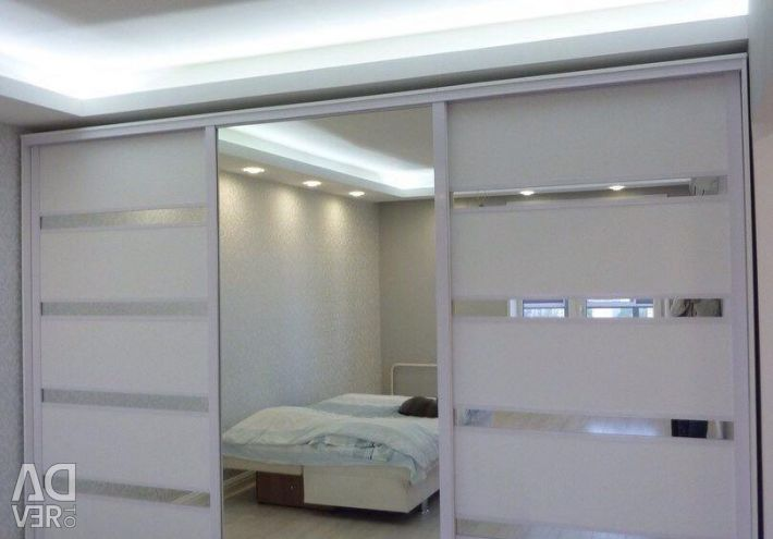 The sliding wardrobe is white. Cabinets and storage furniture