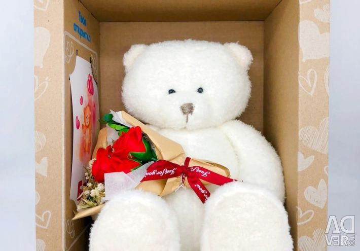Teddy bear with a bouquet in a gift box